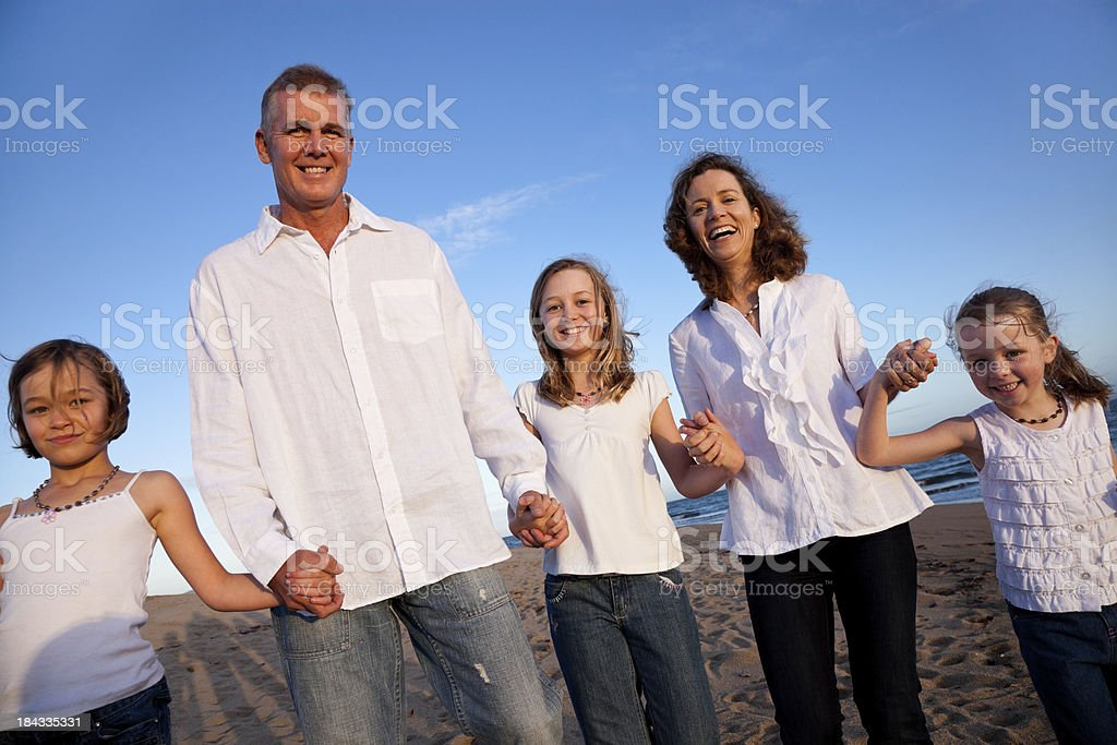 Happy Family of Five in white at beach blue sky royalty-free stock photo