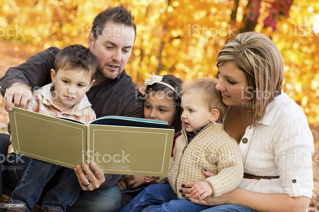 Happy Family of Five Reading Outdoors on Fall Day royalty-free stock photo