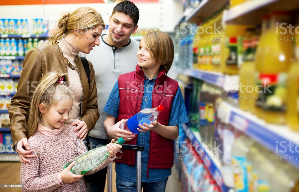 Happy family of four buying mineral water stock photo