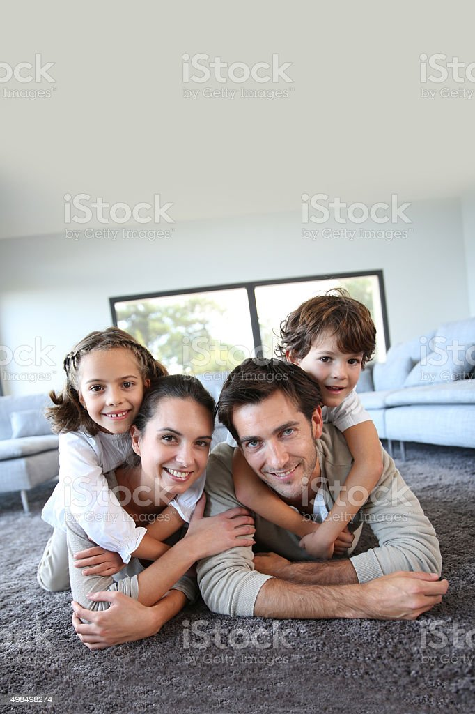 Happy family of four laying on floor stock photo