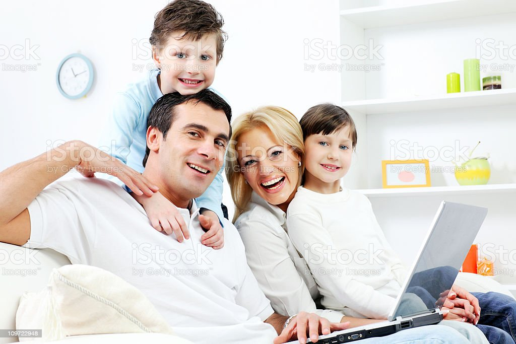 Happy family of four people sitting with laptop computer royalty-free stock photo