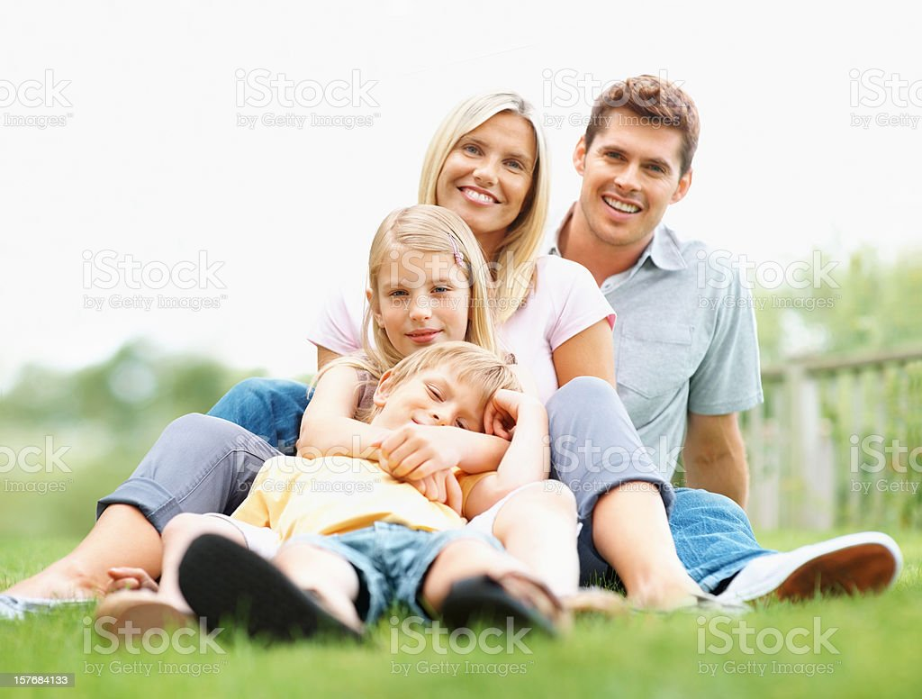 Happy family of four relaxing together on grass royalty-free stock photo