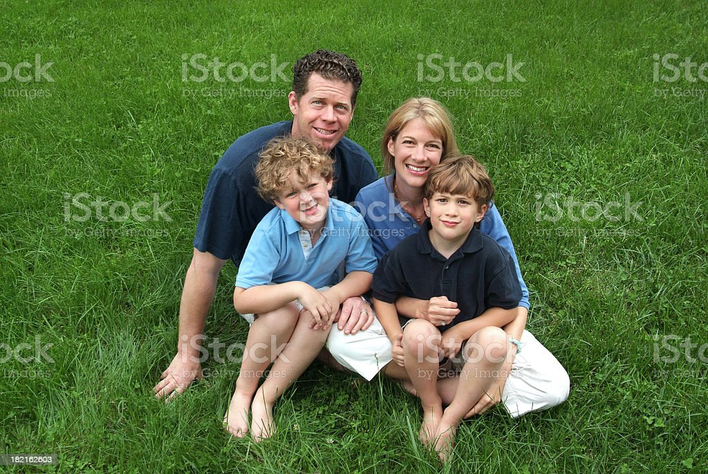 Happy Family of Four Sitting in the Green Grass royalty-free stock photo