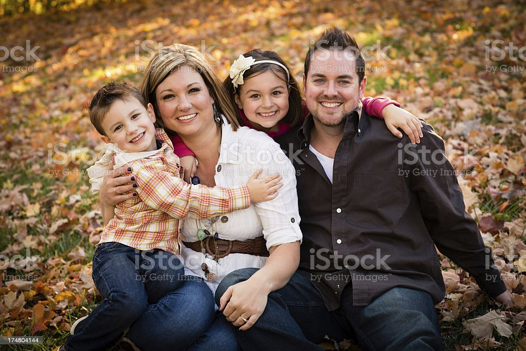 Happy Family of Four Sitting Outside on Sunny, Fall Day royalty-free stock photo