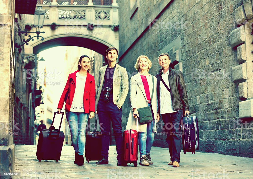 Happy family of four with trunks and bags stock photo