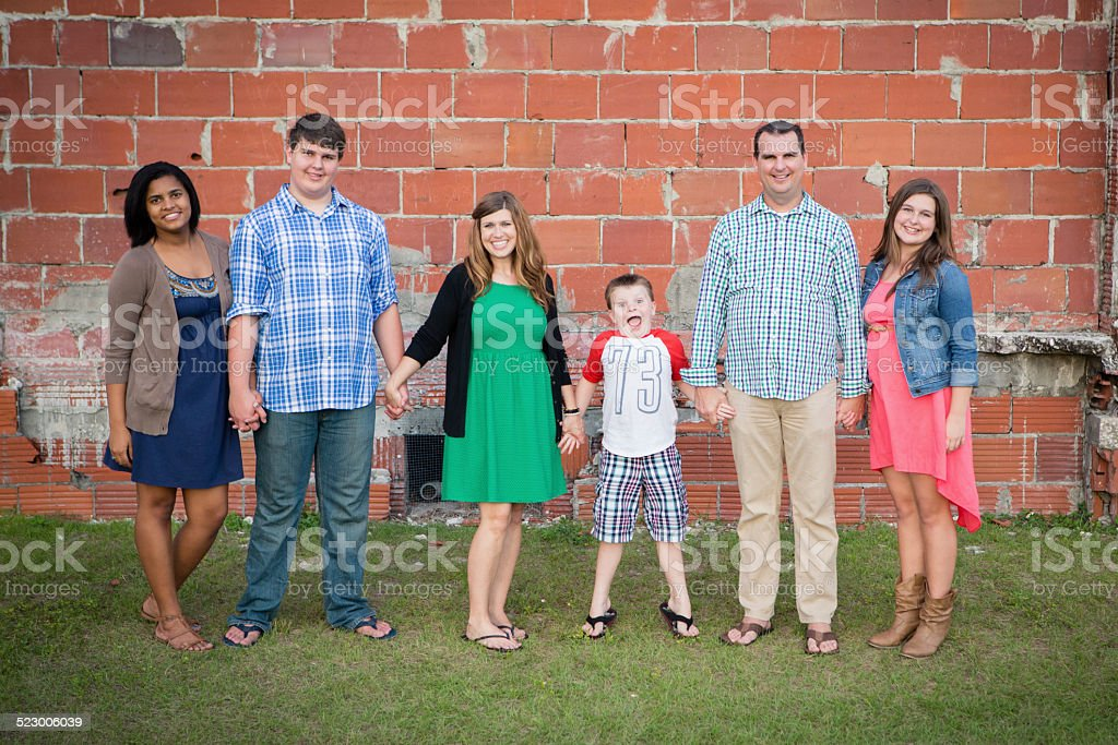 Happy Family of Six Holding Hands Together Outside stock photo