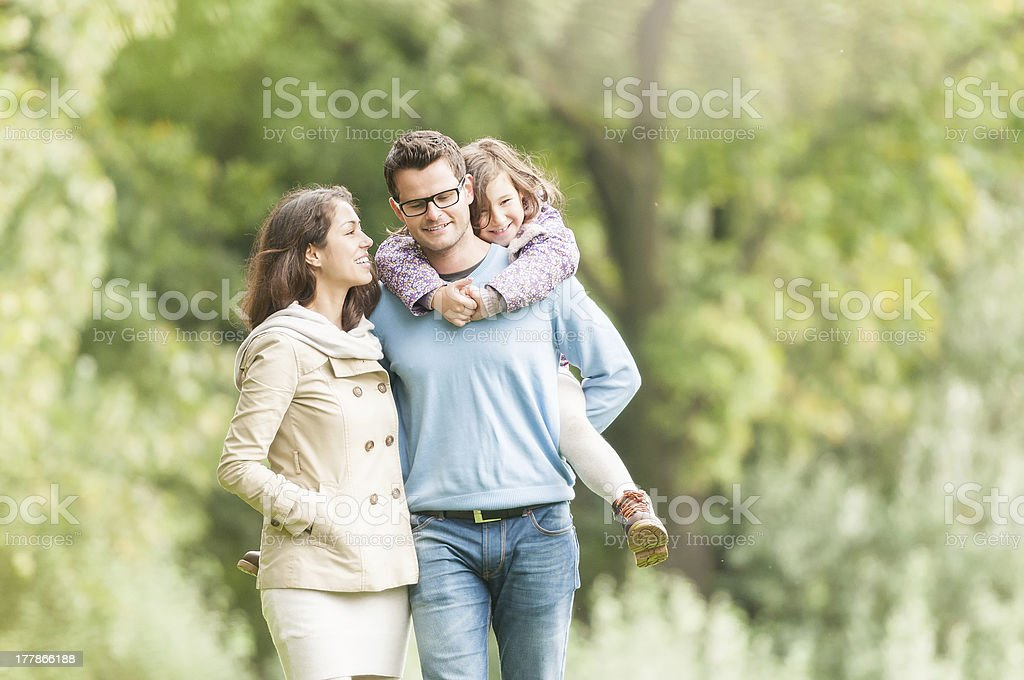 Young happy family of three having fun together outdoor. Pretty...