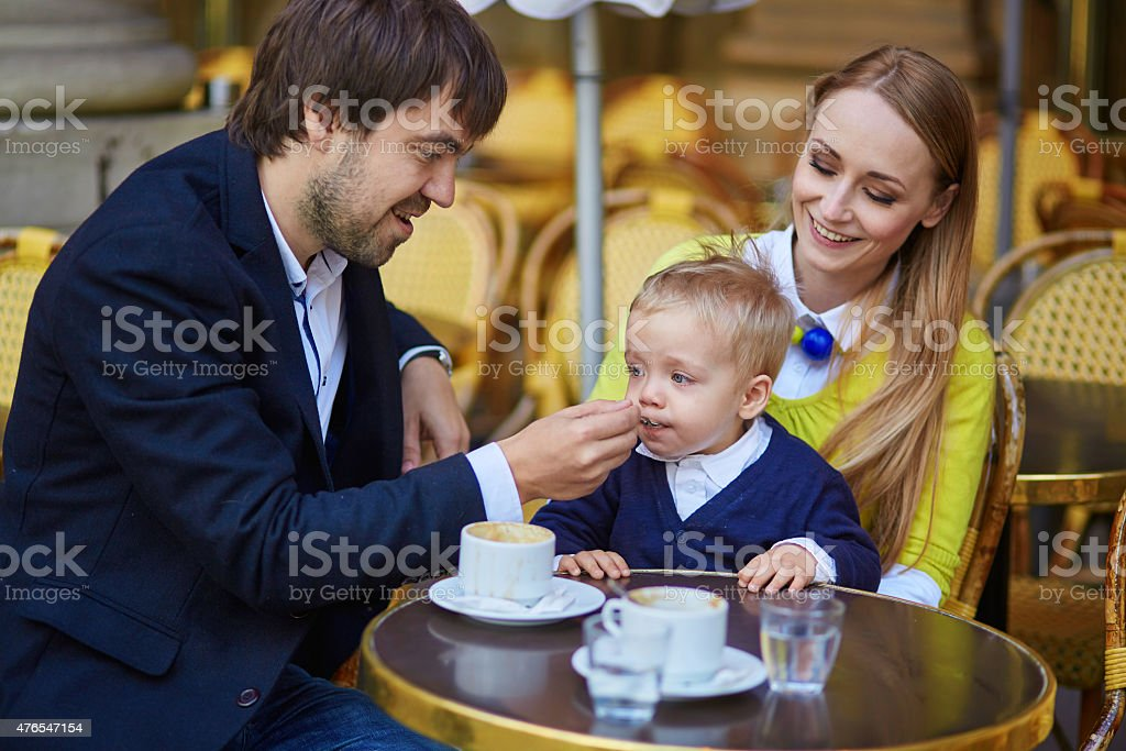 Happy family of three in cafe stock photo