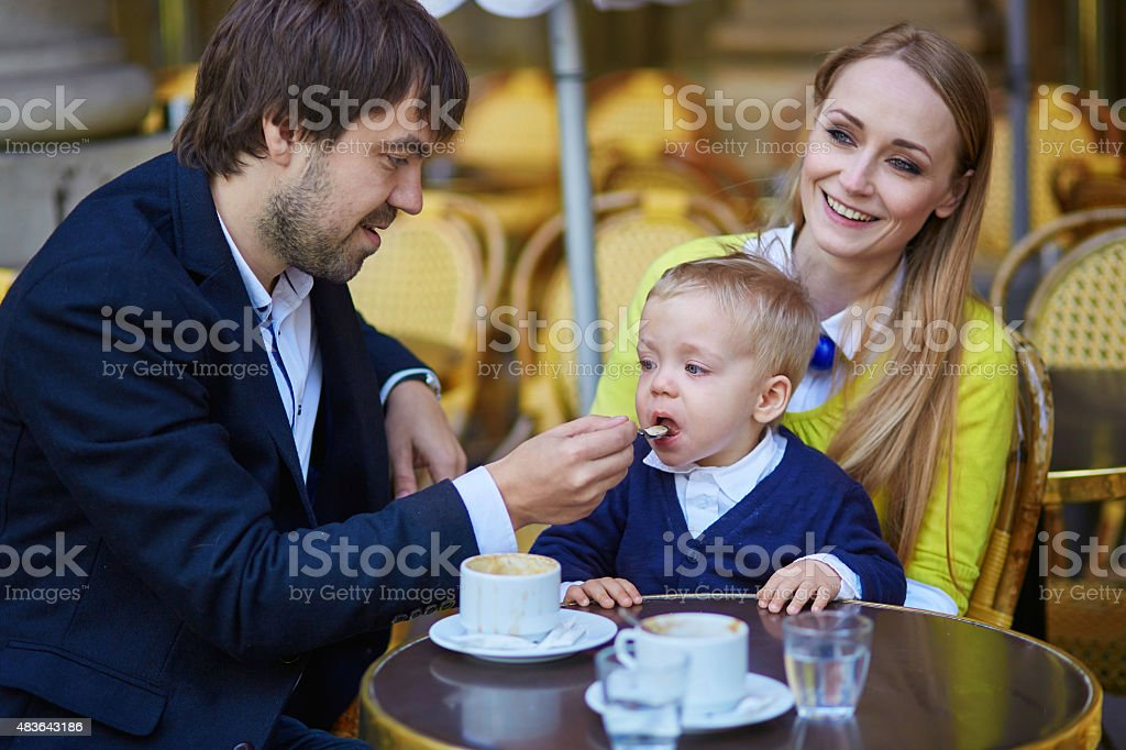 Happy family of three in Parisian cafe stock photo