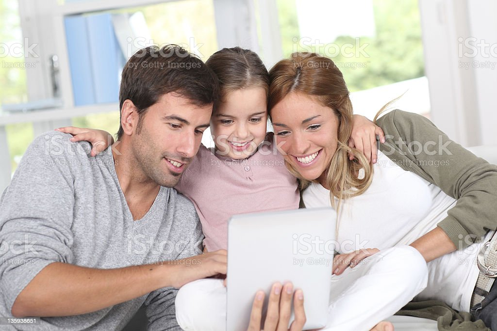 Happy family of three looking at a tablet screen royalty-free stock photo
