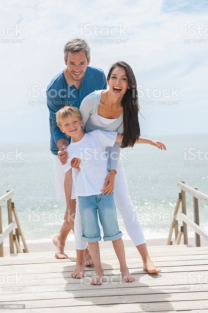 happy family of three persons in front of the sea stock photo