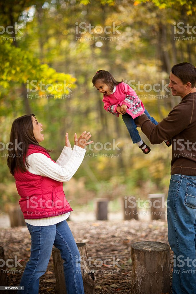 Happy Family of Three Playing in the Autumn Woods royalty-free stock photo