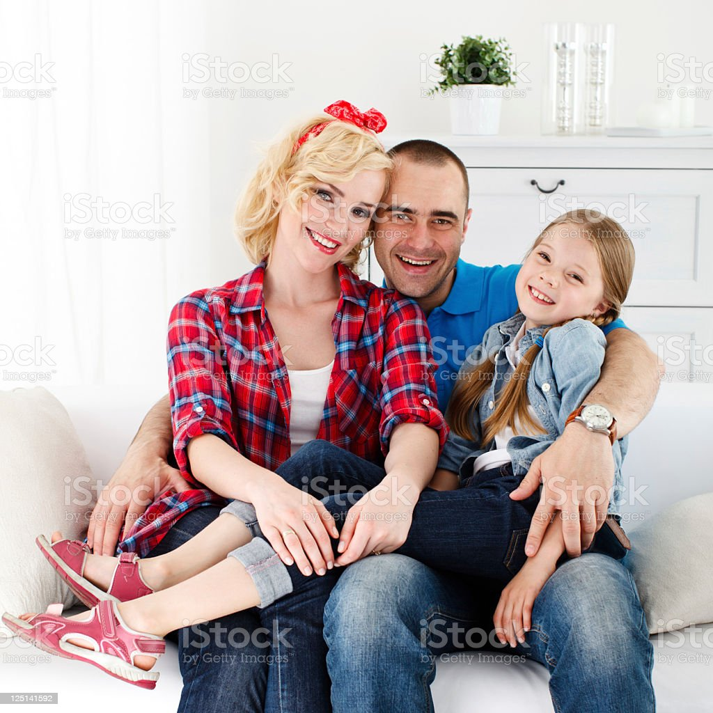Happy Family of Three Posing on a Couch royalty-free stock photo