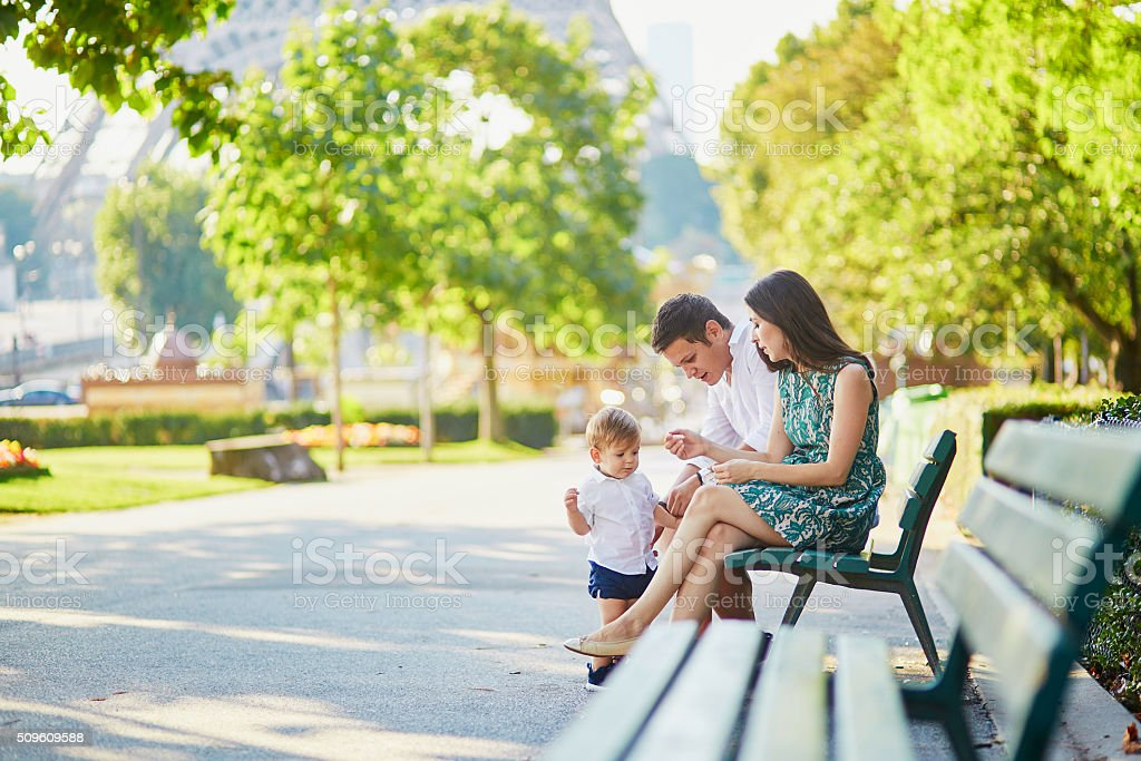 Happy family of three sitting near the Eiffel tower stock photo