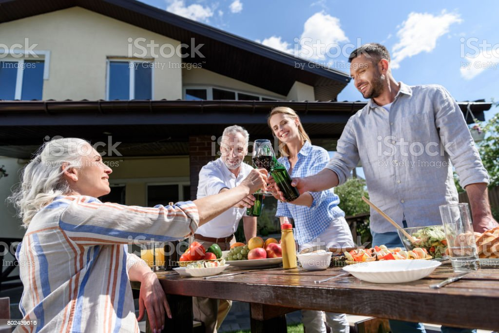 happy family of two generations clinking glasses and bottles with alcohol drinks together stock photo