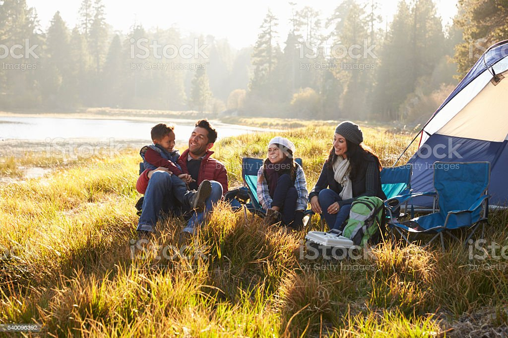 Happy family on a camping trip relaxing by their tent stock photo