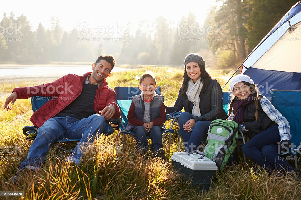 Happy family on a camping trip sit by tent looking stock photo