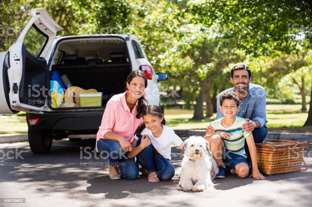 Happy family on a picnic sitting next to their car stock photo