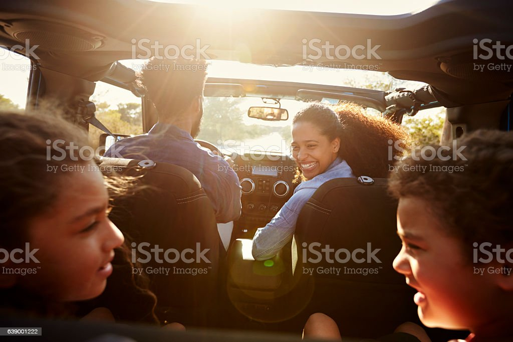 Happy family on a road trip in their car, rear passenger stock photo