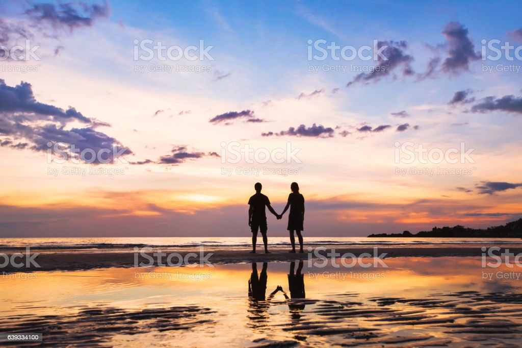 happy family on the beach, silhouette of couple at sunset stock photo