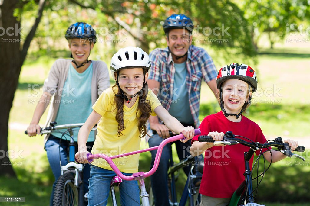 Happy family on their bike at the park stock photo