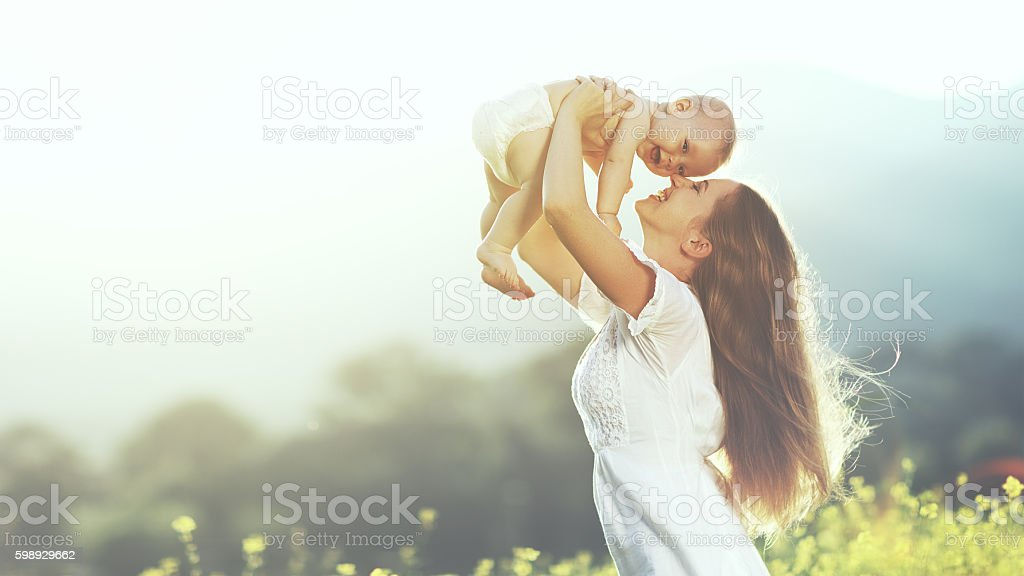 happy family outdoors. mother throws baby up, laughing and playi stock photo