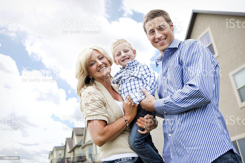 Happy family outside of housing development stock photo