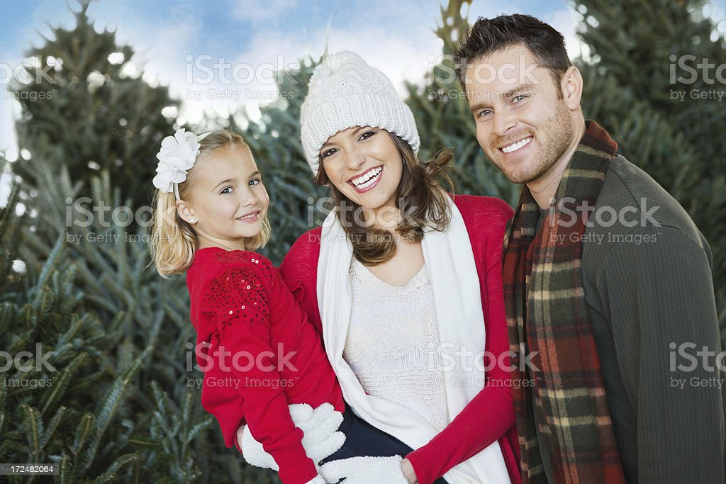 Happy family picking out Christmas tree to buy at farm royalty-free stock photo