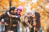 Happy family piggybacking in autumn at the park.