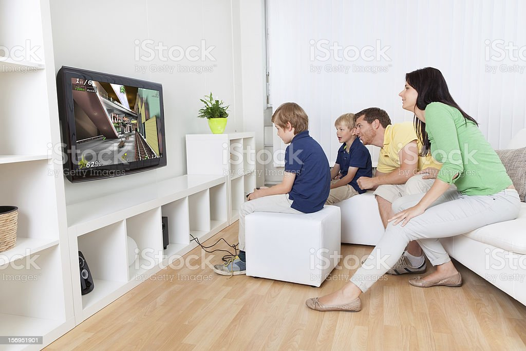 Happy family playing a videogame stock photo