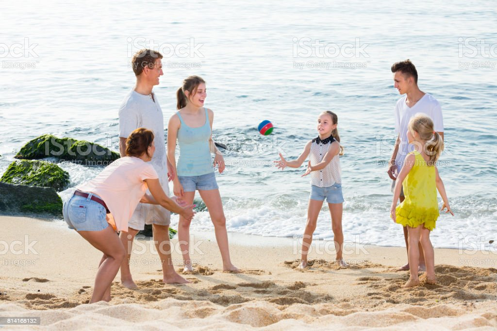 Happy family playing active games on beach stock photo