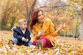 Happy family playing and having fun at autumn park
