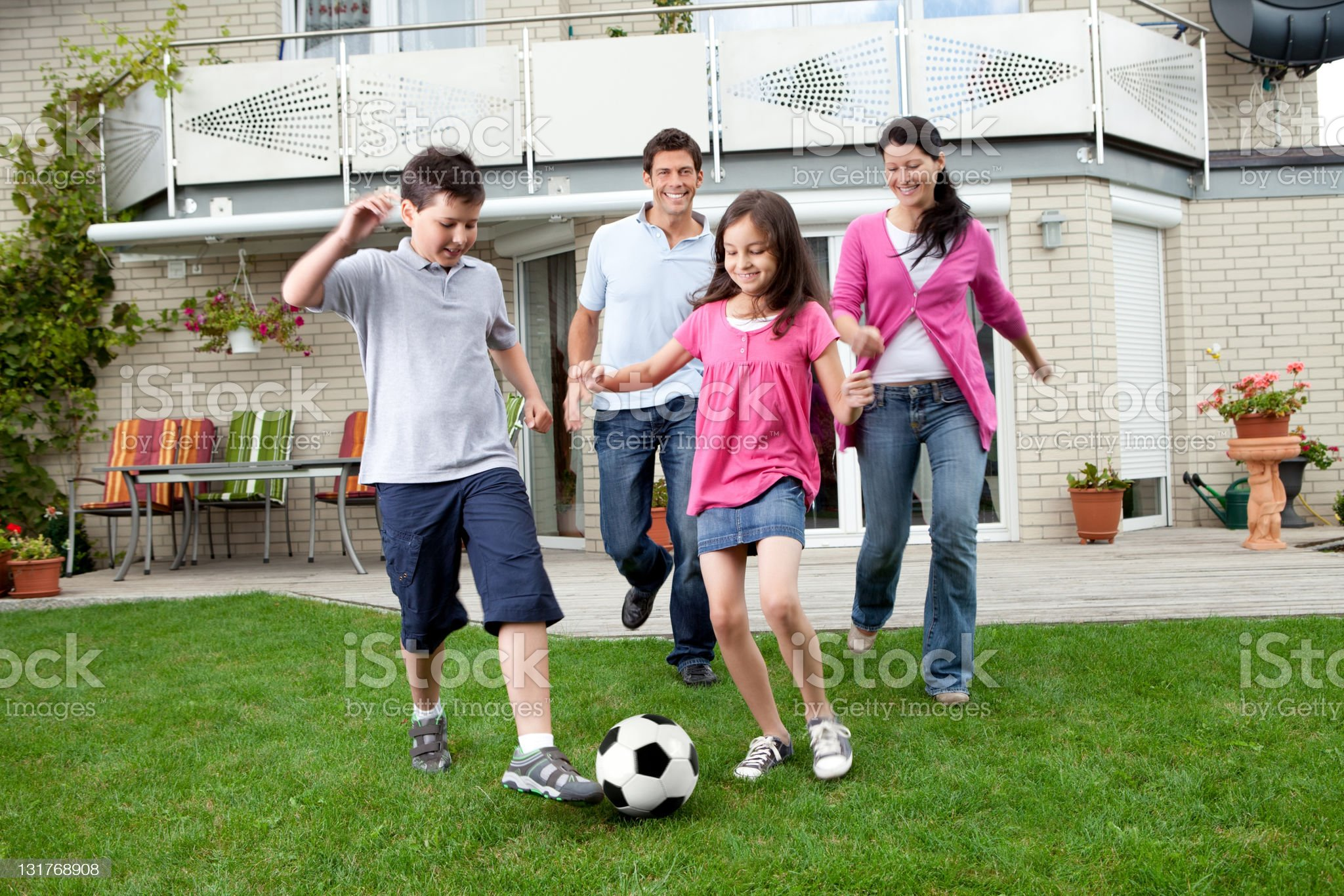 Happy family playing football in their backyard royalty-free stock photo