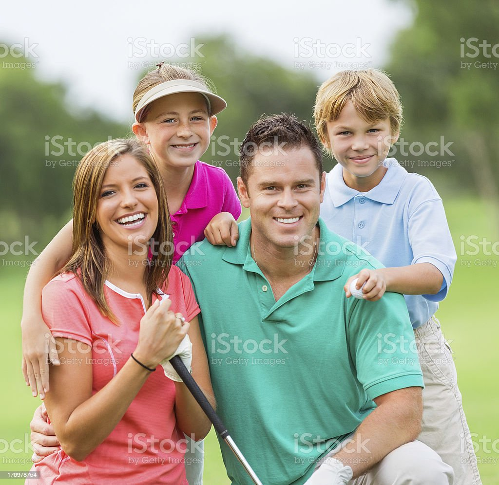 Happy family playing golf together on green course royalty-free stock photo