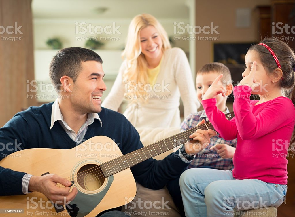 Happy family playing guitar at home royalty-free stock photo