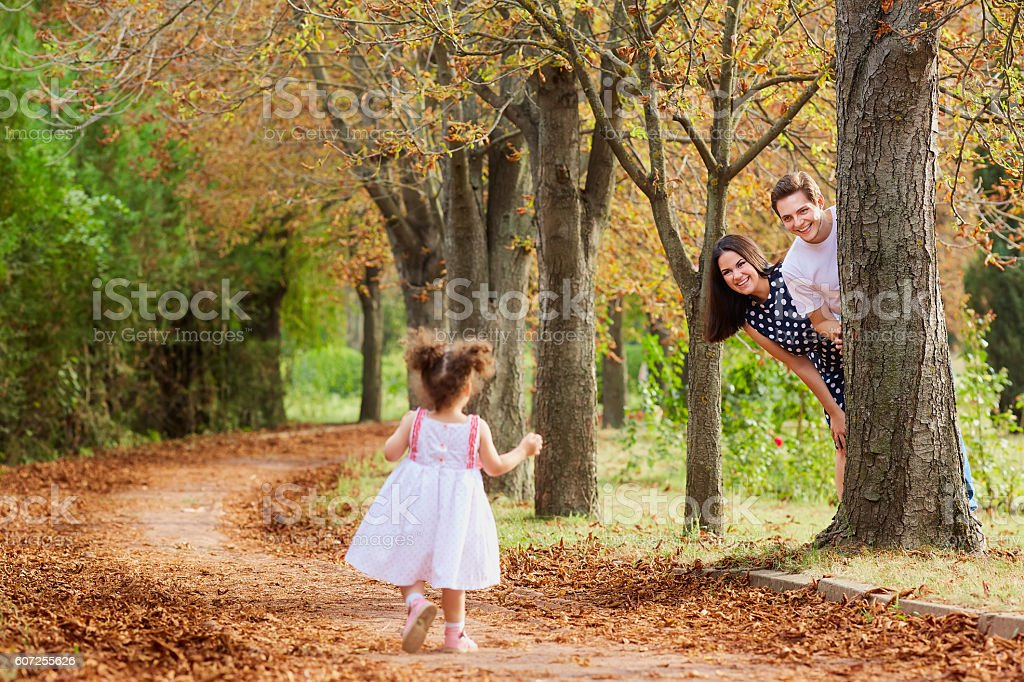 Happy family playing in the park on autumn alley, summer. stock photo