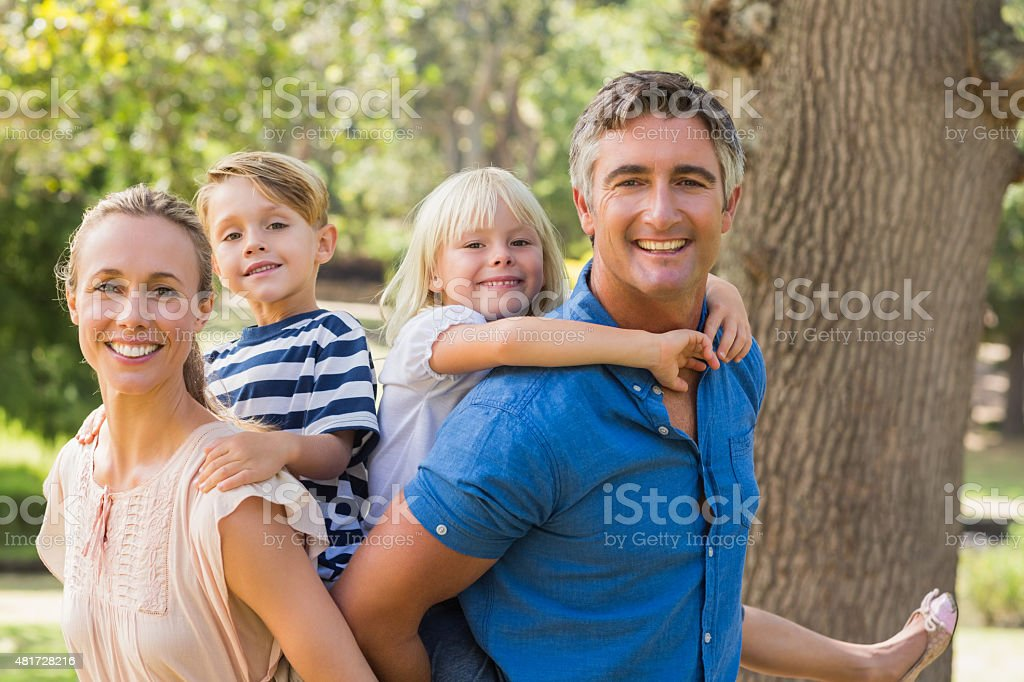 Happy family playing in the park together stock photo