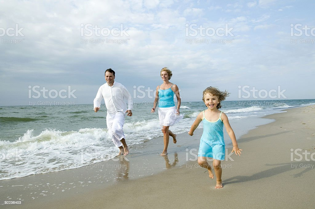 Happy family playing on the beach royalty-free stock photo