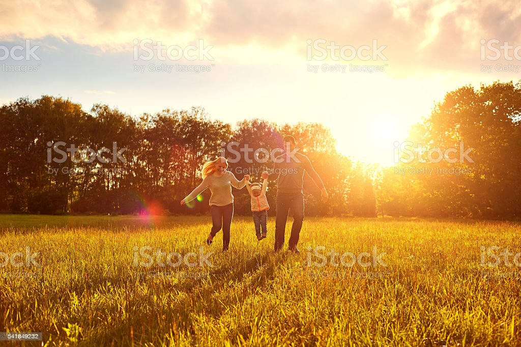 Happy family playing on the grass in  park  evening. stock photo