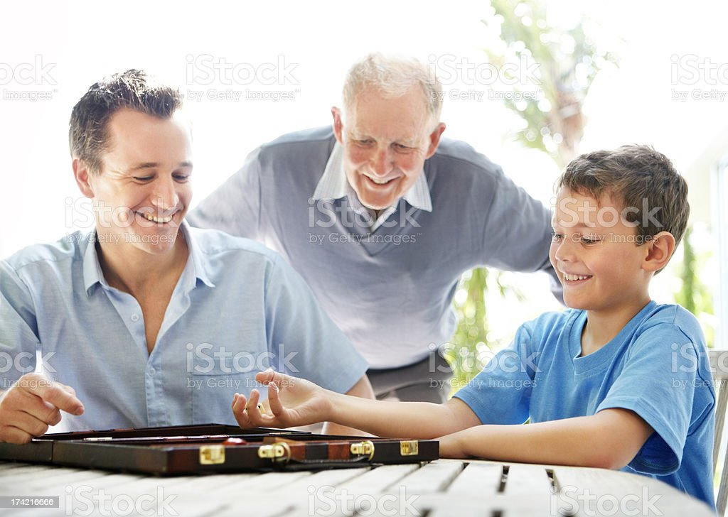 Happy family playing together a game of backgammon stock photo