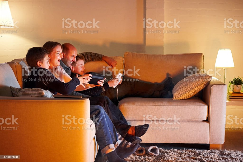 Happy family playing video game at home stock photo