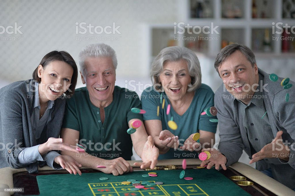 Happy family playing with casino chips stock photo