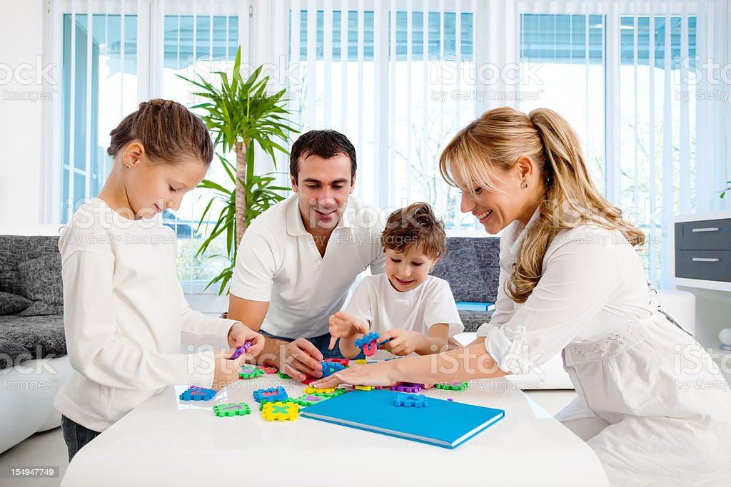 Happy family playing with puzzle at home. royalty-free stock photo