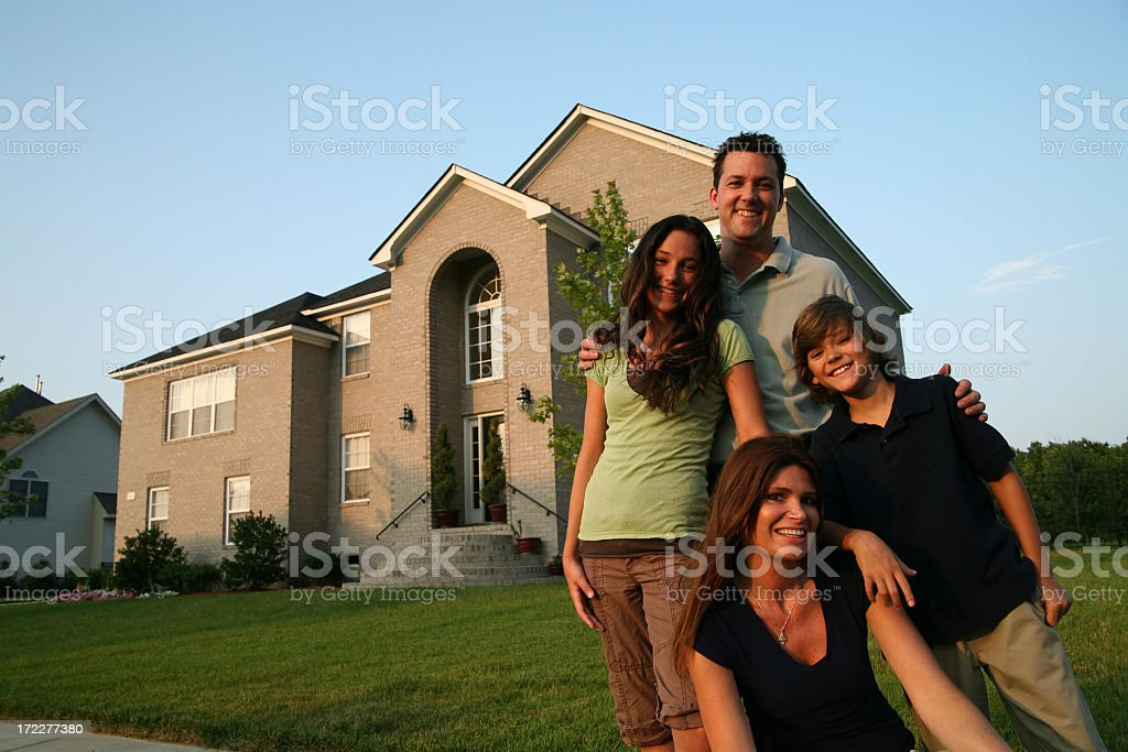 Happy family posing in front of a house stock photo
