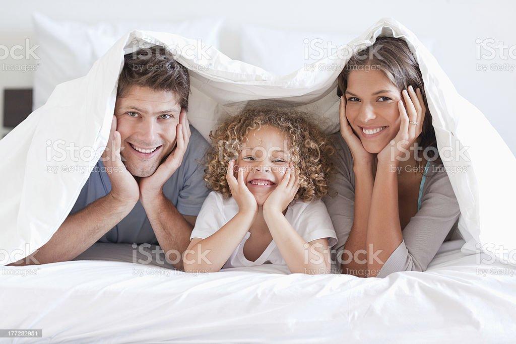 Happy family posing under a duvet royalty-free stock photo