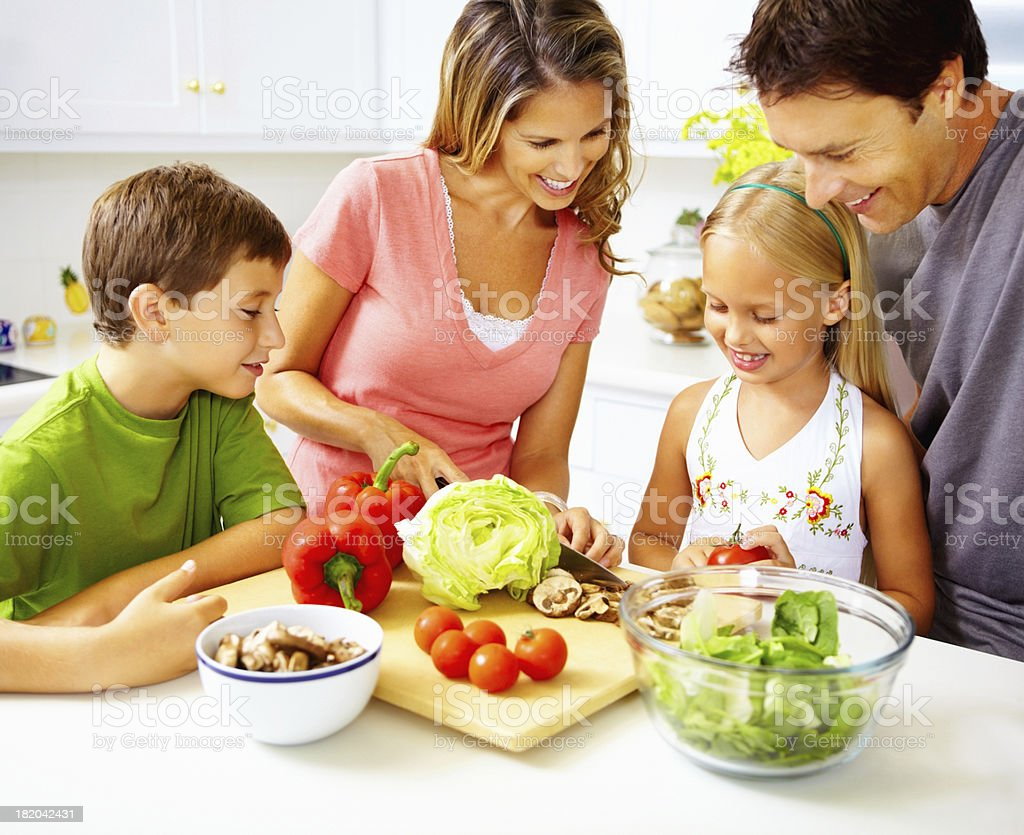 Happy family preparing meal together in the kitchen stock photo