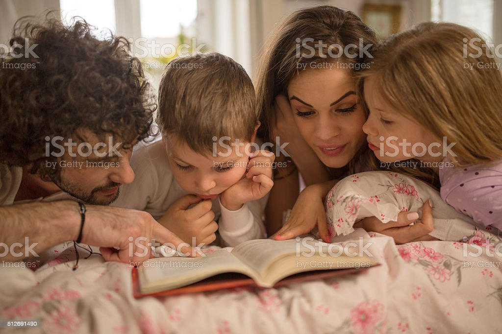 Happy family reading a story together in bed. stock photo