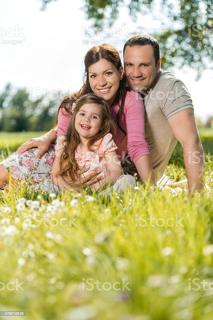 Happy family relaxing in grass during spring day. stock photo