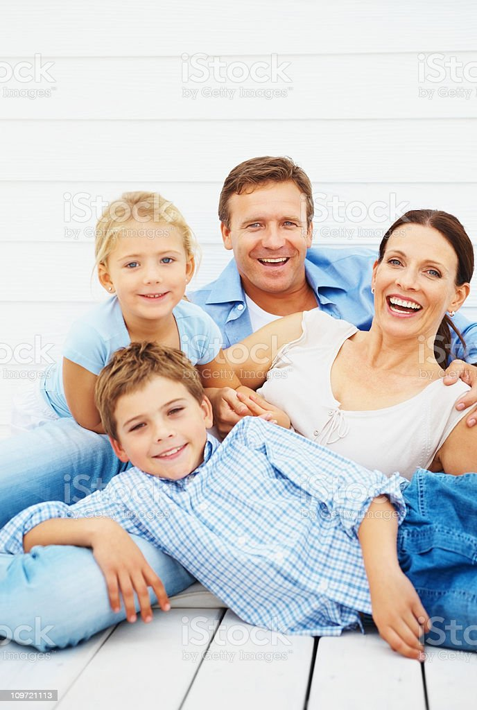 Happy family relaxing outdoors against wall royalty-free stock photo