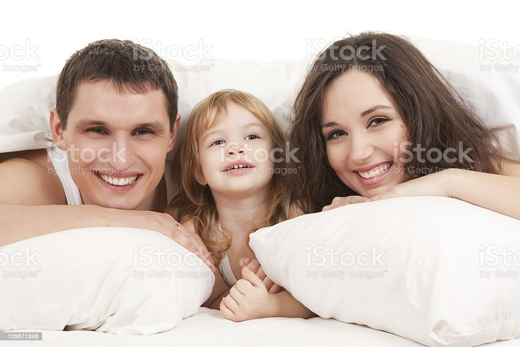 Happy family resting on the white bed royalty-free stock photo